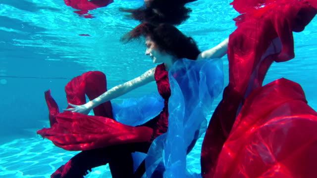 Una-chica-guapa-nada-y-bailes-bajo-el-agua-en-la-piscina-en-un-vestido-rojo-con-tela-roja-y-azul-en-sus-manos-mira-a-la-cámara-y-sonríe-Cámara-lenta-
