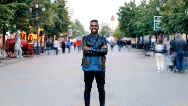 Zoom-in-time-lapse-of-happy-African-American-guy-wearing-jeans-and-leather-jacket-standing-alone-in-street-downtown-smiling-and-looking-at-camera-with-crowd-moving-by-