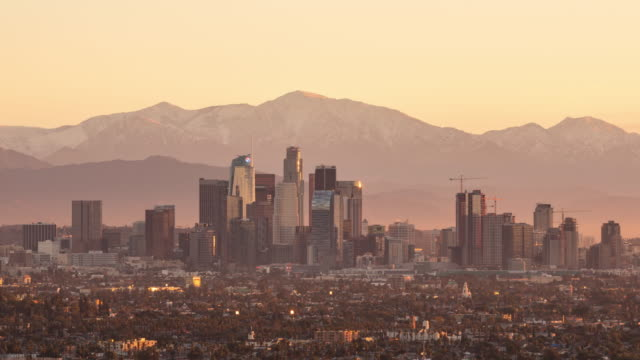 Downtown-Los-Angeles-Skyline-With-Snowy-Mountains-Sunrise-Timelapse-Close
