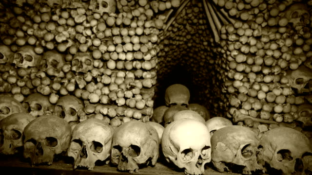4K-footage-of-Human-s-bones-and-skulls-in-the-underground-catacombs-with-old-chronicle-film-effect-after-processing-