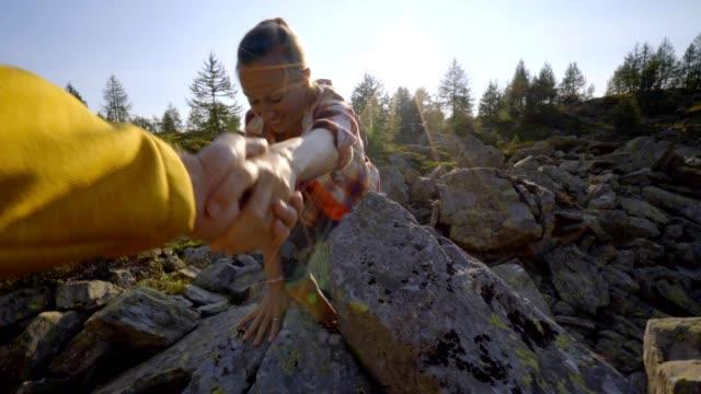 Su-compañero-de-equipo-ayudar-a-senderista-para-llegar-a-la-Cumbre-Pareja-en-Suiza-mano-llegar-a-excursionista-mujer-llegar-a-la-Cumbre-Ayuda-concepto-de-mano
