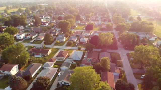 Vista-aérea-de-casas-residenciales-en-verano-Barrio-americano-suburbio-Bienes-raíces-disparos-de-drones-amanecer-luz-solar-desde-arriba-