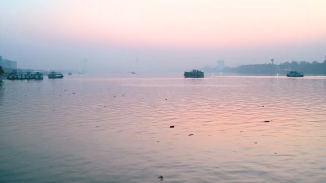 Boat-moving-over-Ganges-river-in-Kolkata-city-at-the-time-of-Sunset-near-Vidyasagar-setu-or-second-Hooghly-Bridge-in-West-Bengal-India-