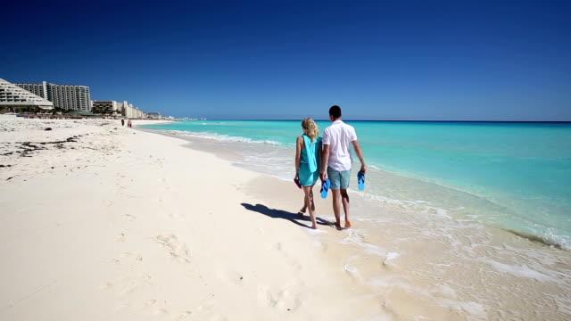 Pareja-joven-con-pantuflas-caminando-por-la-playa