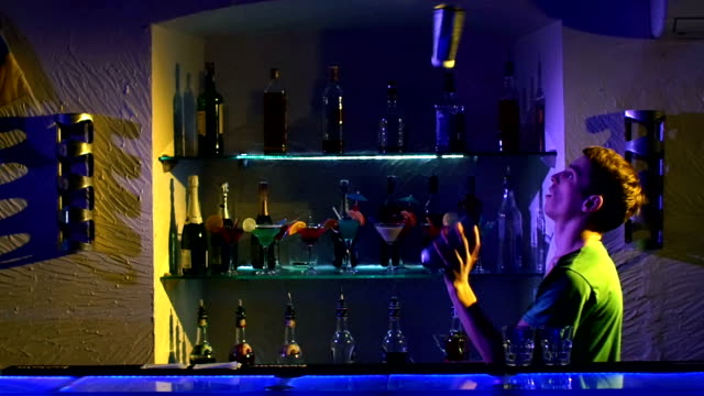 Professional-bartender-making-cool-amazing-tricks-three-shakers-juggling-standing-behind-the-bar-catching-throwing-up-slow-motion