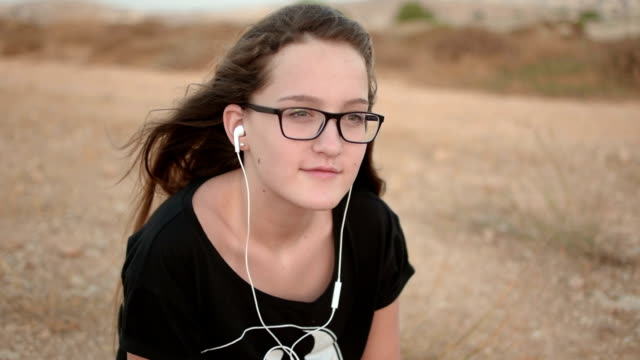 Teenage-girl-with-glases-sitting-on-the-ground-listening-to-the-music-outdoor