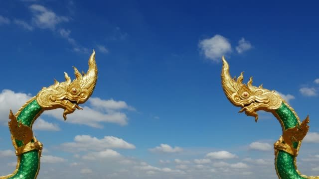 Dragon-statues-facing-each-other-at-Nakhon-Phanom-Thailand-Naga-symbol-of-protection-Time-lapse-moving-clouds-against-clear-blue-sky-