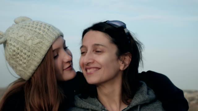 Familienporträt-der-glücklichen-Mutter-und-der-Teenager-Tochter-lächelt-umarmt-zeigt-Liebesaufnahmen-