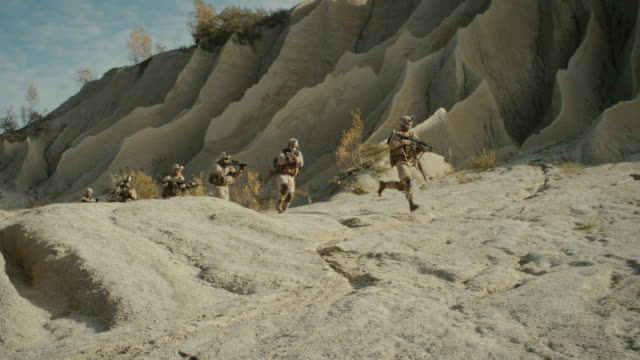 Escuadrón-de-soldados-armados-y-totalmente-equipados-que-corren-en-el-desierto-