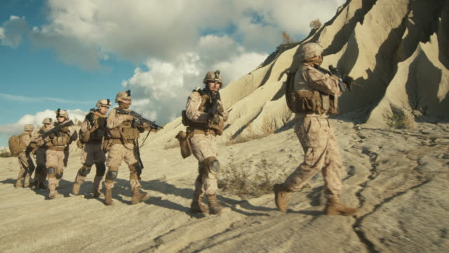 Squad-of-Fully-Equipped-and-Armed-Soldiers-Walking-in-Single-File-in-the-Desert-