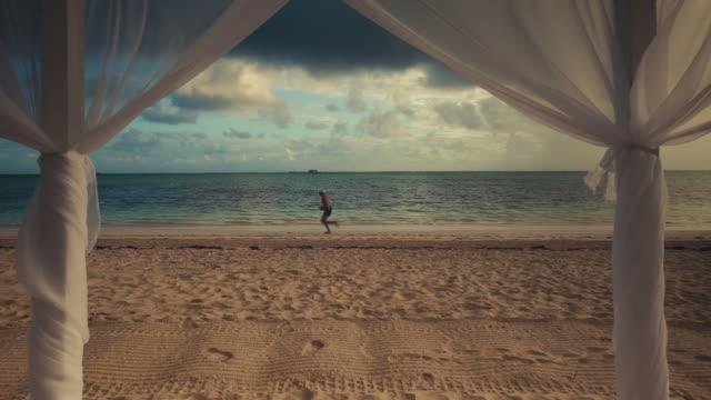 Tropical-island-beach-sunrise-and-running-man-on-the-sand-in-Punta-Cana