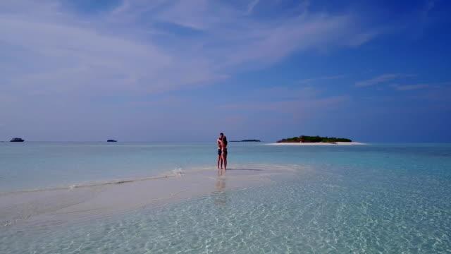 v03962-vuelo-drone-vista-aérea-de-Maldivas-playa-2-personas-pareja-hombre-mujer-amor-romántico-en-la-isla-de-paraíso-tropical-soleado-con-cielo-azul-aqua-agua-mar-4k