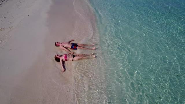 v03975-vuelo-drone-vista-aérea-de-Maldivas-playa-2-personas-pareja-hombre-mujer-amor-romántico-en-la-isla-de-paraíso-tropical-soleado-con-cielo-azul-aqua-agua-mar-4k