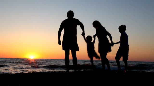 family-silhouette-at-sunset-near-the-sea-mother-dad-Kids