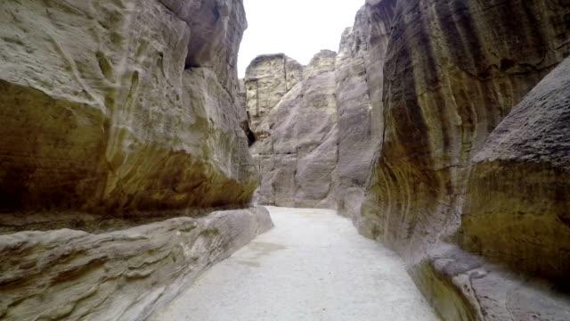 Turistas-caminando-por-el-cañón-de-Petra-Vista-de-la-ciudad-de-Petra-en-Jordania-Ruta-turística-de-Petra-en-Jordania-Ciudad-tallada-en-la-montaña-