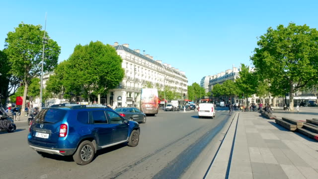 Morning-traffic-with-city-tour-bus-at-Place-de-la-Republique-and-bronze-statue-of-Marianne-holding-olive-branch-is-in-the-square-center