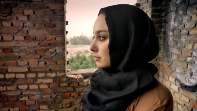 Joven-mujer-musulmana-triste-en-hijab-en-edificios-abandonados-dando-vuelta-y-mirando-a-cámara-concepto-de-miedo-y-terror-terrorismo