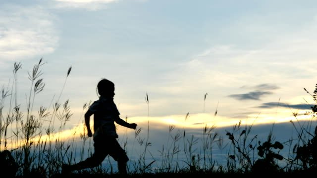 Little-boy-two-old-7-years-Happy-with-a-running-and-jump-on-meadow-in-summer-in-nature-Sunset-time-4K-Video-Slow-motion