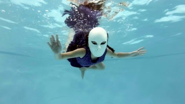 Un-niño-en-una-máscara-de-hadas-blancas-nada-y-plantea-bajo-el-agua-en-un-vestido-púrpura-mira-a-la-cámara-y-agitando-sus-manos-sobre-un-fondo-azul-Cámara-lenta-