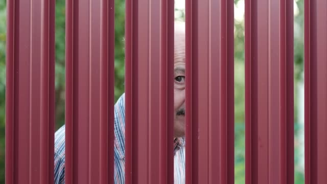 Senior-man-looking-through-fence-spying-on-his-neighbor