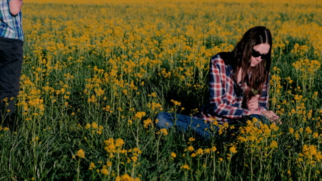 Boy-gives-his-mother-a-bouquet-of-wild-flowers-and-kisses-her-sitting-on-the-grass-among-the-yellow-flowers-