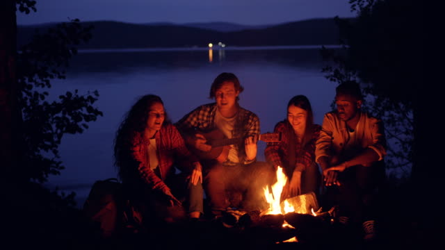 Happy-and-relaxed-guys-and-girls-are-singing-while-their-friend-is-playing-the-guitar-near-campfire-in-forest-near-lake-at-night-Nature-recreation-and-music-concept-