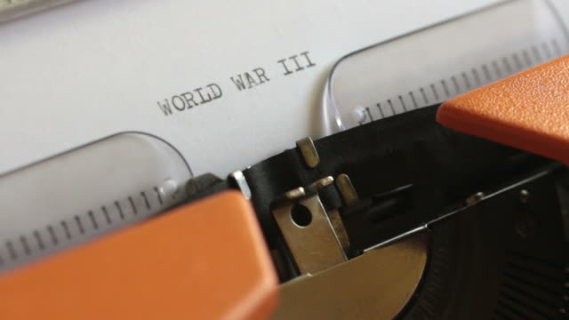 Close-up-footage-of-a-person-writing-WORLD-WAR-III-on-an-old-typewriter