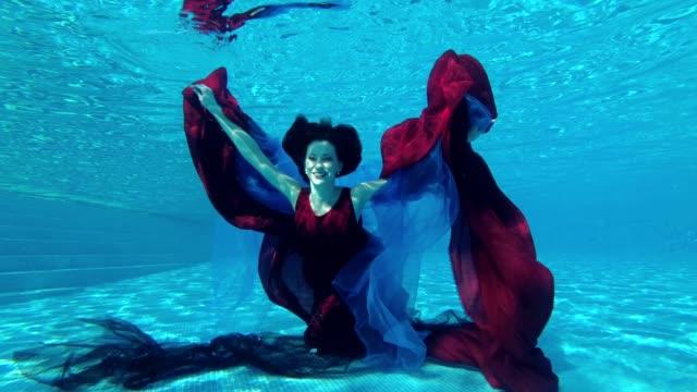 Feliz-novia-chica-de-vestido-rojo-se-sumerge-bajo-el-agua-hasta-el-fondo-de-la-piscina-con-paño-rojo-y-azul-en-sus-manos-Mira-a-la-cámara-y-sonríe-Cámara-lenta