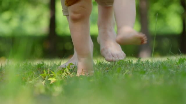 Legs-of-Woman-and-Baby-Walking-on-Grass-Barefoot