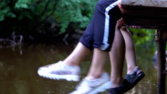 Adolescentes-se-relaja-por-el-río-sentado-en-el-borde-de-un-embarcadero-de-madera-