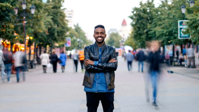 Zoom-out-time-lapse-of-emotional-African-American-man-standing-in-street-with-arms-crossed-and-looking-at-camera-when-men-and-women-are-whizzing-by-