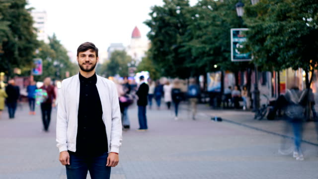 Time-lapse-of-good-looking-bearded-guy-looking-at-camera-and-smiling-standing-in-the-street-downtown-then-stepping-back-while-men-and-women-are-moving-near-him-