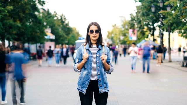 Zoom-out-time-lapse-of-confident-young-lady-in-sunglasses-looking-at-camera-standing-in-busy-pedestrian-street-in-flow-of-people-Youth-and-society-concept-
