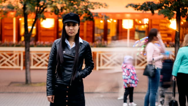 Time-lapse-portrait-of-tired-Asian-girl-standing-in-pedestrian-street-with-hand-in-pocket-and-looking-at-camera-then-leaving-men-and-women-are-whizzing-around-