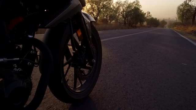 cinematic-shot-of-a-motorcycle-rider-in-a-sunset-time-crossing-the-road-in-the-forest-seeing-some-many-parts-of-the-motorcycle-and-the-sky-and-the-trees-camera-is-taking-the-wheel-crossing-the-road-between-the-fog