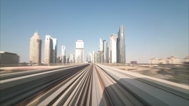 Viaje-de-lapso-de-tiempo-en-la-moderna-Dubai-sin-conductor-elevado-sistema-de-Metro-tren-corriendo-hacia-adelante-junto-a-la-carretera-del-Jeque-Zayed