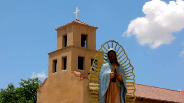 Statue-of-the-Our-Lady-of-Guadalupe-Standing-Peacefully-in-front-of-an-Adobe-Church