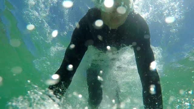 LENTA-cerca:-Pato-alegre-joven-surfista-bucear-bajo-la-ola