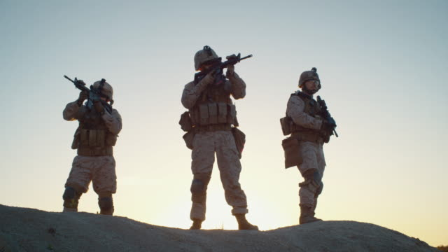 Squad-of-Three-Fully-Equipped-and-Armed-Soldiers-Standing-on-Hill-in-Desert-Environment-in-Sunset-Light-Slow-Motion-