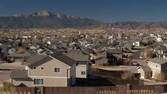 ANTENA-fila-casas-de-lujo-en-la-ciudad-suburbana-con-montañas-rocosas-en-el-fondo