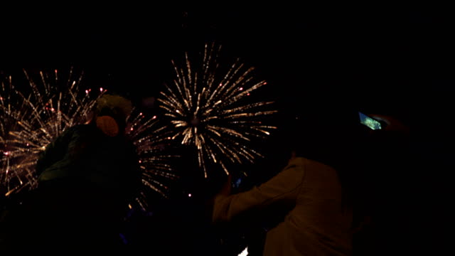 Little-girl-sitting-on-your-dad-s-shoulders-and-watching-fireworks-Concept-of-family-relationships-and-Father-s-day-Viewers-take-pictures-on-smartphone-Firework---concept-of-finale-of-any-holiday:-Chinese-new-year-New-year-Christmas-wedding