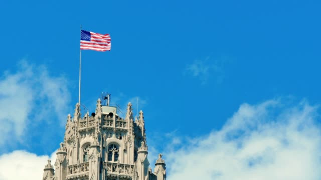 United-States-of-America-Flag-Waving-on-the-Top-of-a-Skyscraper