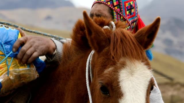 Quechua-man-loading-horse-