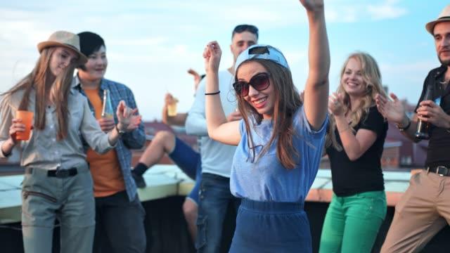 Joven-bailando-en-medio-de-multitudes-con-levantar-los-brazos-en-la-fiesta-en-la-azotea