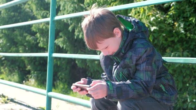 El-niño-juega-un-juego-en-su-teléfono-móvil-mientras-está-sentado-en-el-parque.