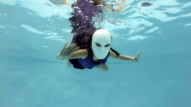 Una-niña-en-una-fabulosa-máscara-blanca-nada-y-plantea-bajo-el-agua-mira-a-la-cámara-y-agitando-sus-manos-