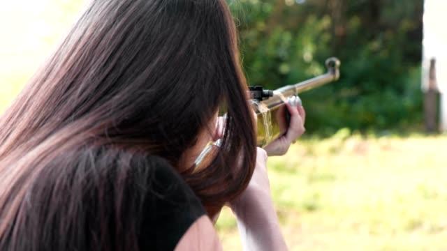 Mujer-dispara-un-arma-de-fuego-Vista-posterior-