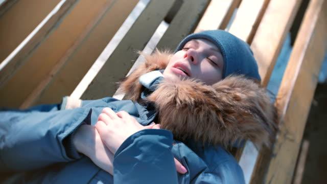 Mujer-hizo-enferma-acostado-en-un-banco-del-parque-en-invierno-y-respirando-pesadamente-