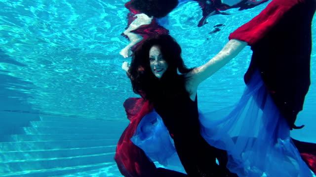 Novia-hermosa-chica-en-vestido-rojo-nada-bajo-el-agua-en-la-piscina-al-aire-libre-con-el-paño-rojo-y-azul-en-sus-manos-Mira-a-la-cámara-y-sonríe-