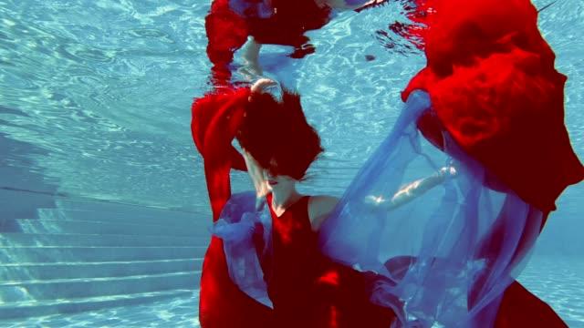 Una-hermosa-muchacha-en-un-vestido-rojo-con-el-pelo-rojo-nada-y-plantea-bajo-el-agua-en-una-piscina-exterior-con-un-paño-rojo-y-azul-en-sus-manos-Mira-a-la-cámara-y-sonríe-Proceso-de-cosecha-